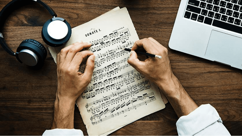 musician reading sheet music with laptop and headphones Music Sync Licensing Companies