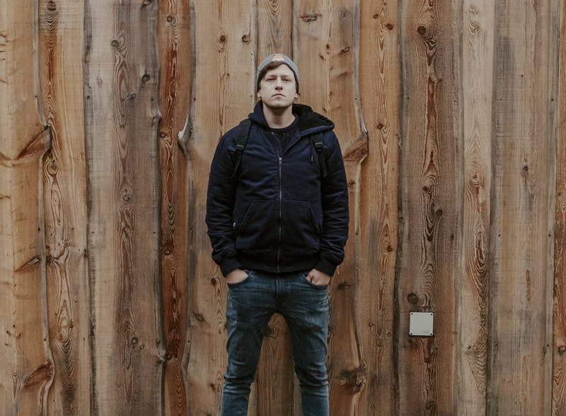 Music producer Tamas standing in front of a wooden wall