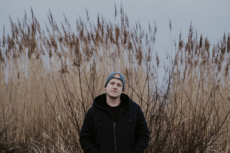 Music producer Tamas standing in front of high grass