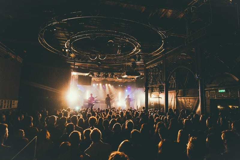 A crowd of people in a music venue watching a band on stage