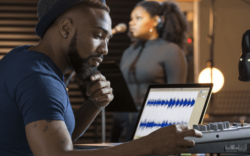 man editing music on laptop