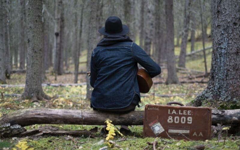 Man playing his guitar in the woods, Chord Progressions 12 bar blues