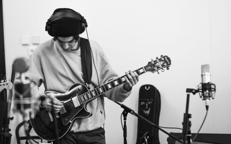musician playing guitar whilst recording in studio