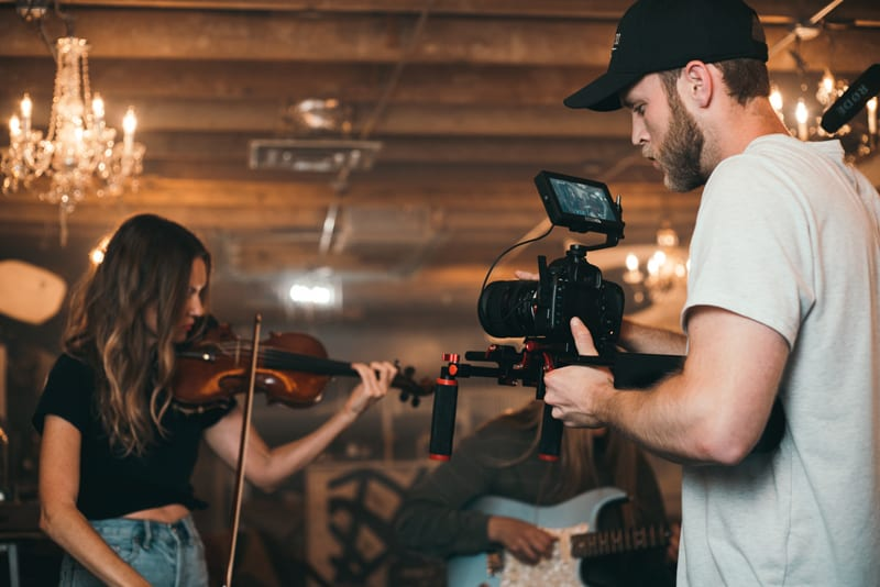 man-holding-camera-and-woman-playing-violin