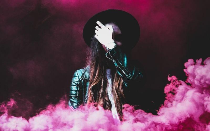 musician wearing hat in pink cloud of smoke