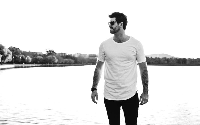 Man in white shirt by lake on white background is MAXO