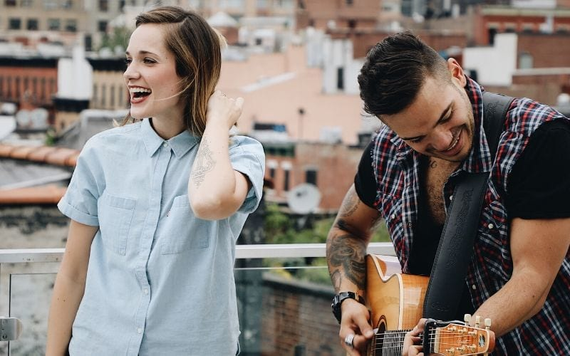 Man and woman, topline writers singing outside with a guitar