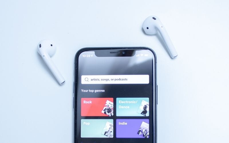 Phone with Air Pods showing Spotify DSP homescreen