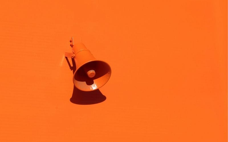 Orange wall with orange speaker or megaphone