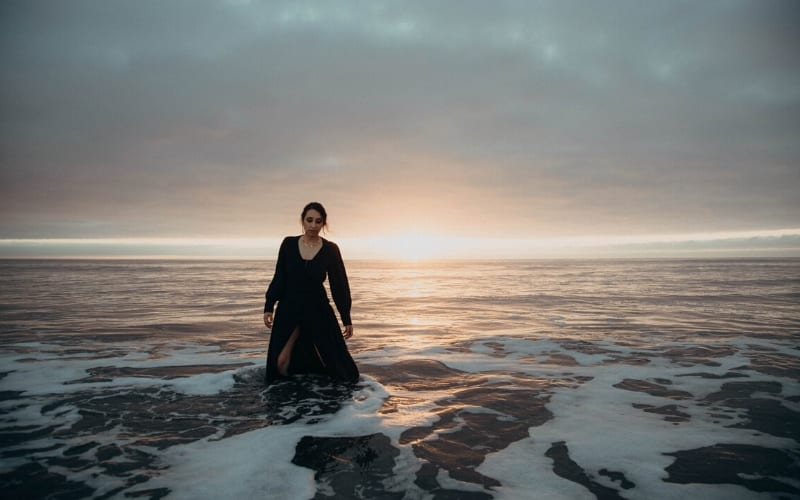 Woman standing in the ocean in front of the sunset in long dress is Naheli
