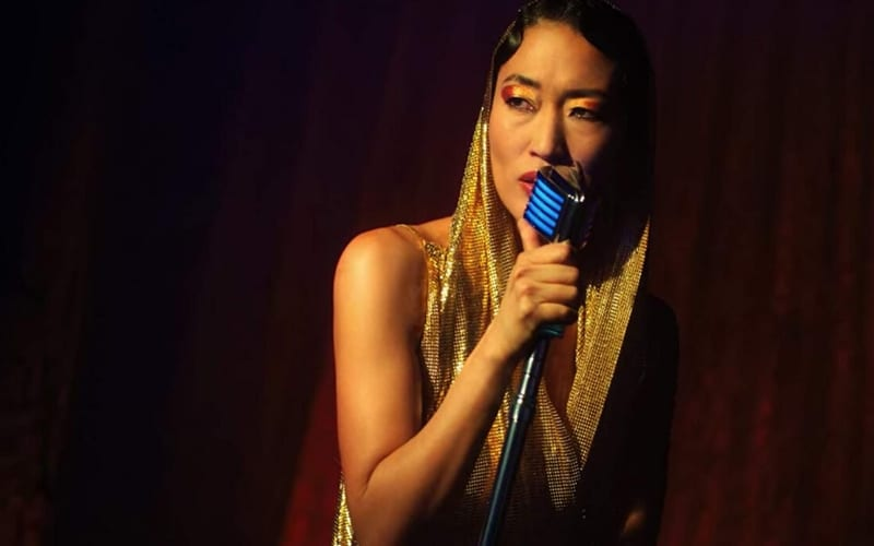 Jihae, dressed in a gold metallic hooded dress, is seen here standing under a spotlight on stage as the Phantom Lady in Altered Carbon