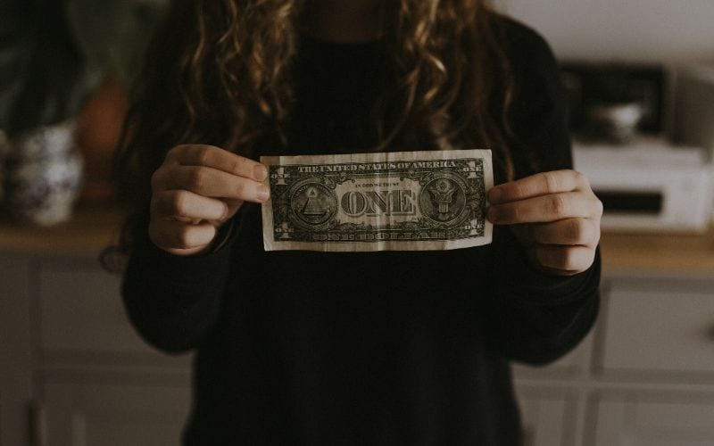 A girl with long curly hair holding a dollar she earned from a music publishing company