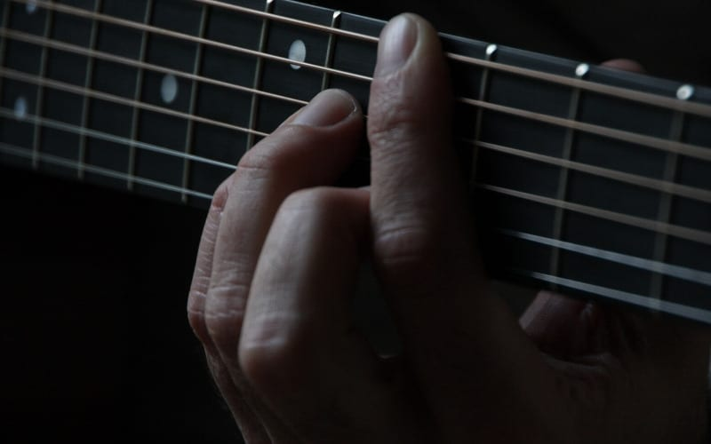 Man playing barre chords on guitar