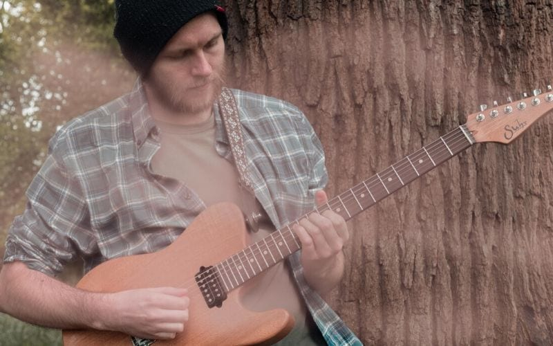 man plying guitar by tree is Darren Wilson Composer