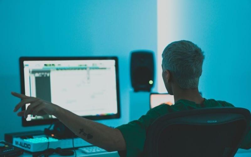 man sat at desk mixing vocal recording
