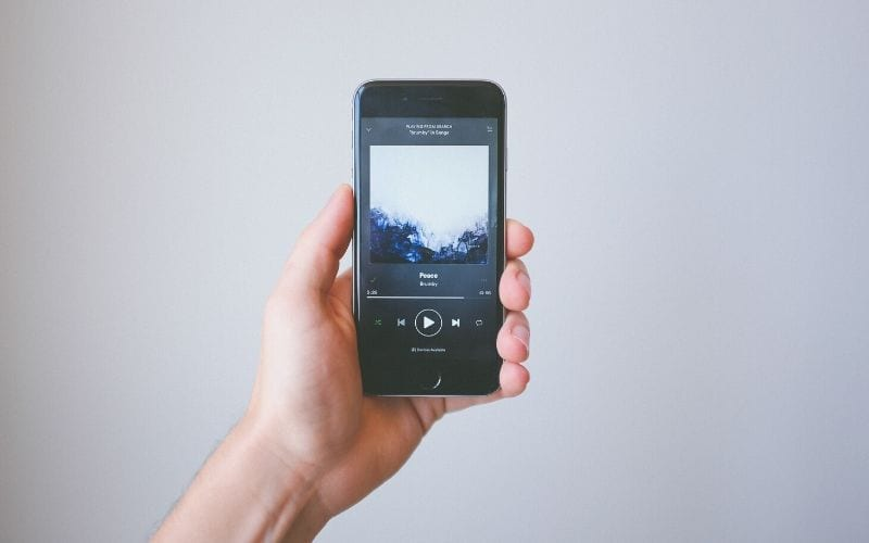 person holding iPhone with Spotify music streaming