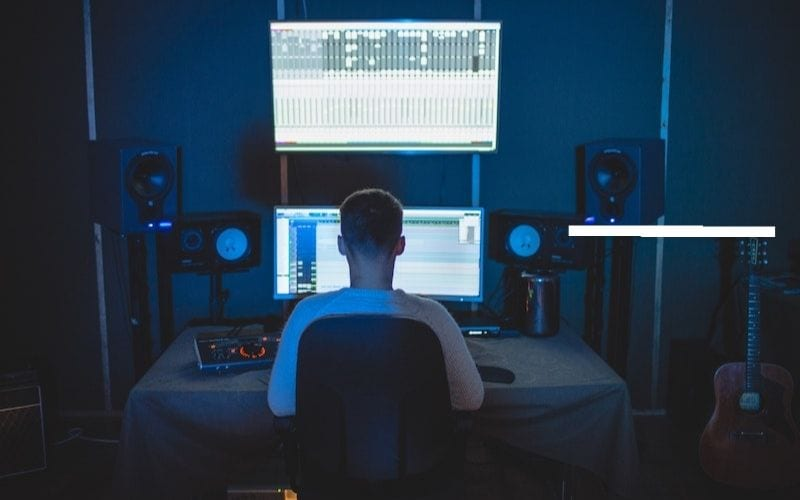 Man at desk music producer using audio compression