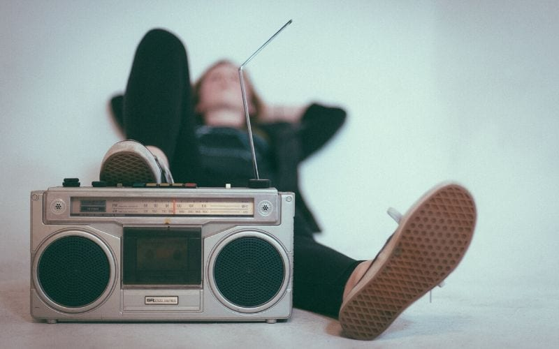 person lying on white ground with foot on Radio