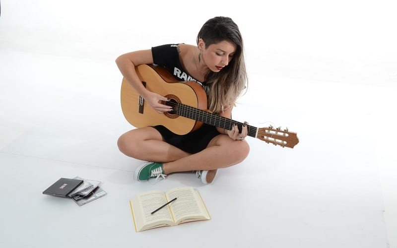 Woman playing guitar and songwriting