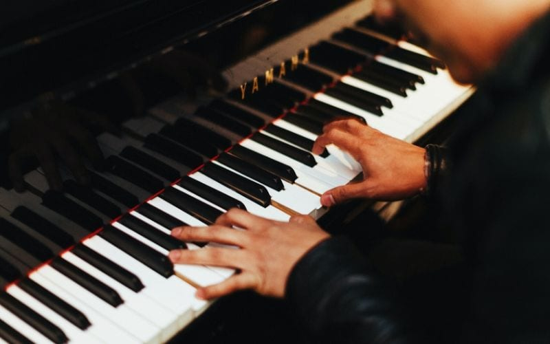 man playing chords on piano