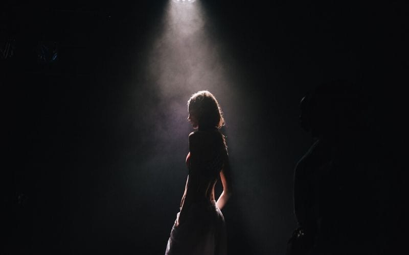 woman on stage with spotlight