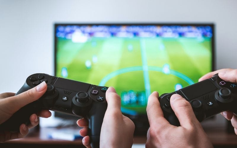 two playstation controllers in front of TV playing FIFA