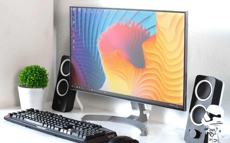 computer on a desk with speakers