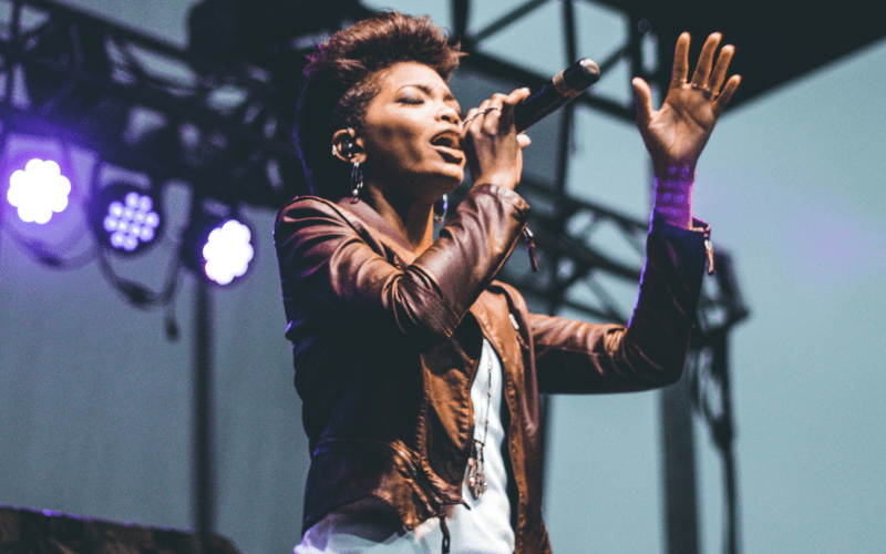 woman on stage singing with microphone