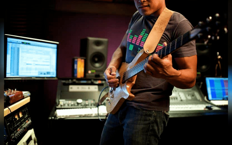 man recording guitars using plug-ins