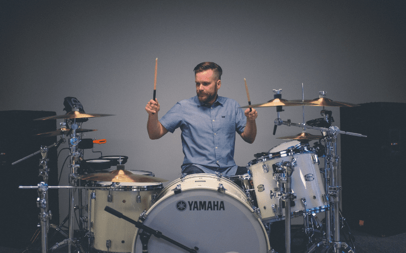 man shows how to set up a drum set