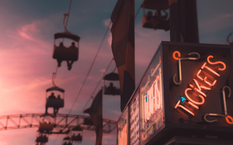 Neon tickets sign with ride in the background.