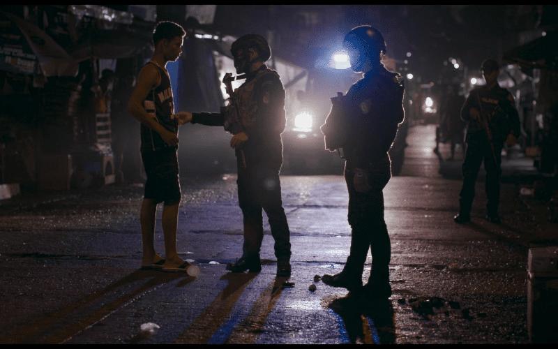 Two armed police talking to a citizen.