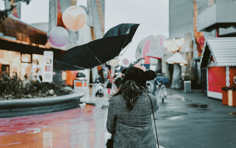woman with broken umbrella on a windy day