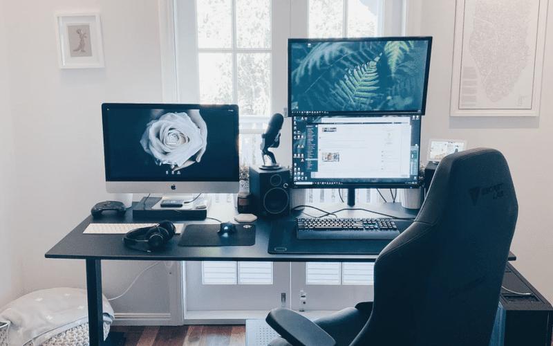 A Gaming chair infront of a desktop set up.