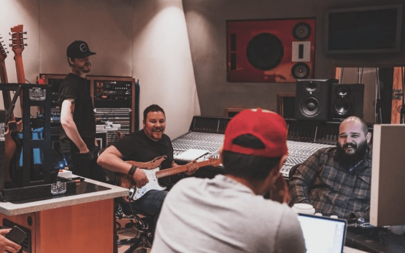 artists in the studio with producer discussing split sheets