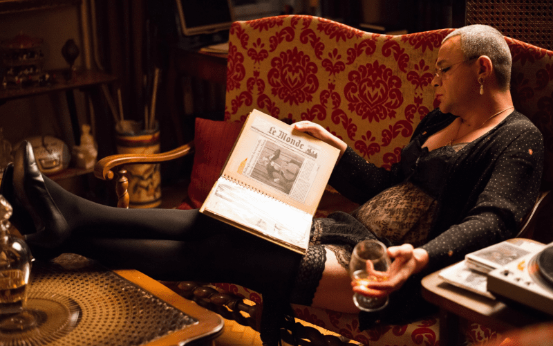 Person relaxing on a sofa reading and having a drink.