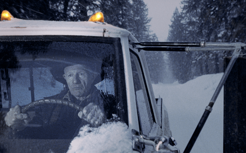 Old man driving his car in the snow.
