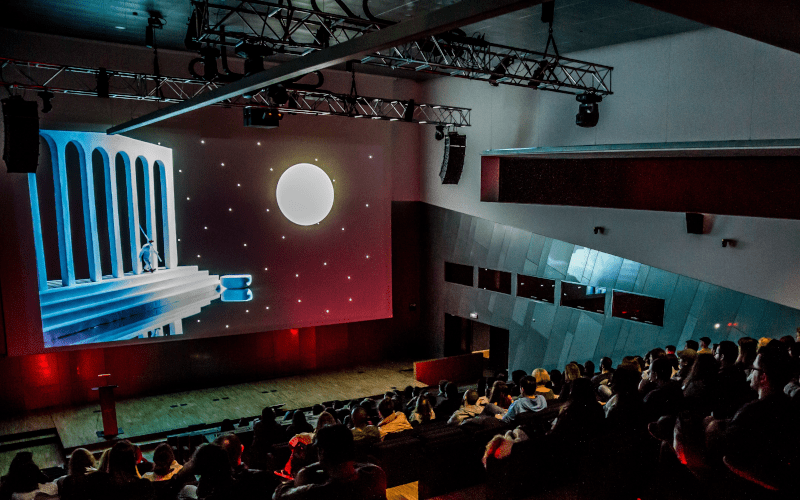 A crowd watching an animated film at Raindance film festival.