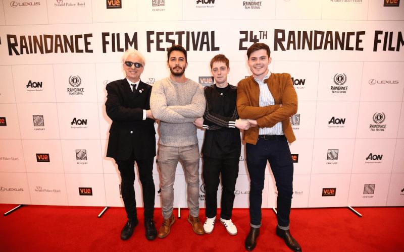 Elliot grove standing with 3 men in front of a Raindance film festival banner.