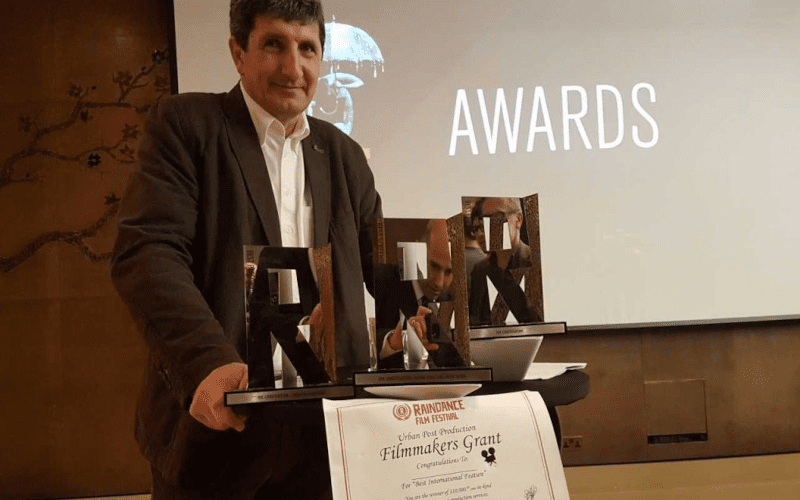 A director standing in front of a presentation with his awards at a Raindance film festival.