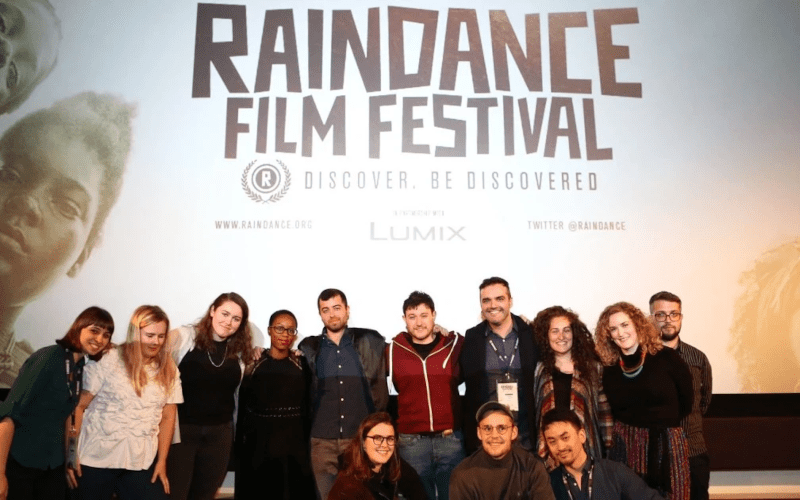 People standing in front of a Raindance film festival banner.