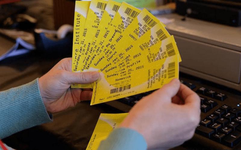 hands holding sundance film festival tickets