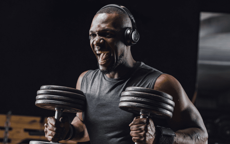 man listening to music lifting dumbells in the gym
