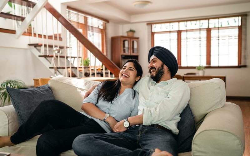 couple on a sofa laughing