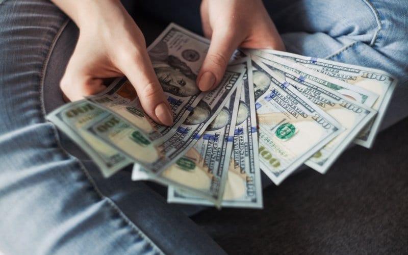person holding 100 dollar bills