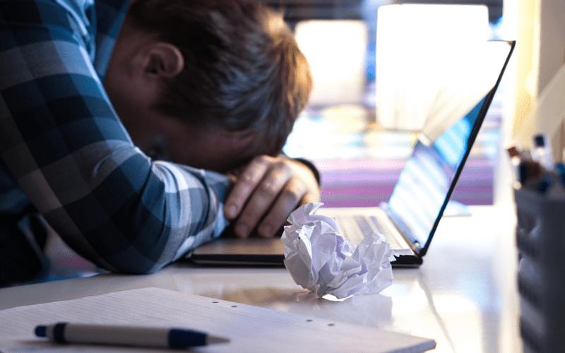 writers block laptop at desk frustration