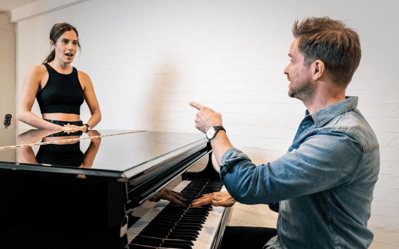 A vocal coach trains a background singer