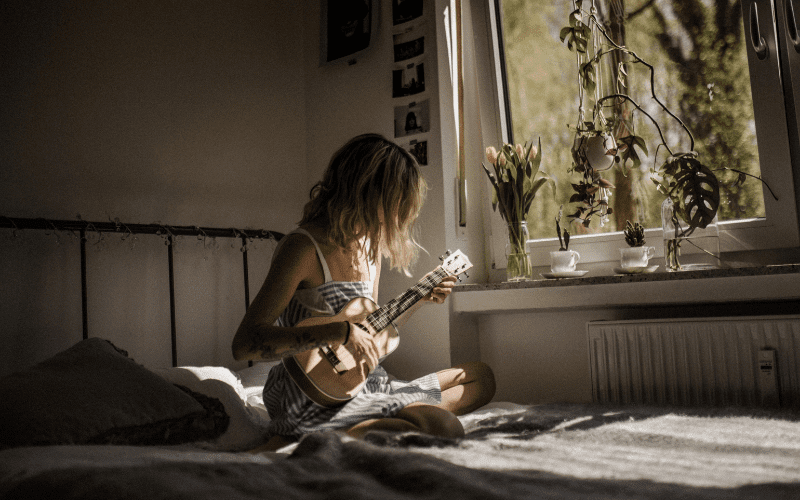 girl playing guitar in bedroom with plants