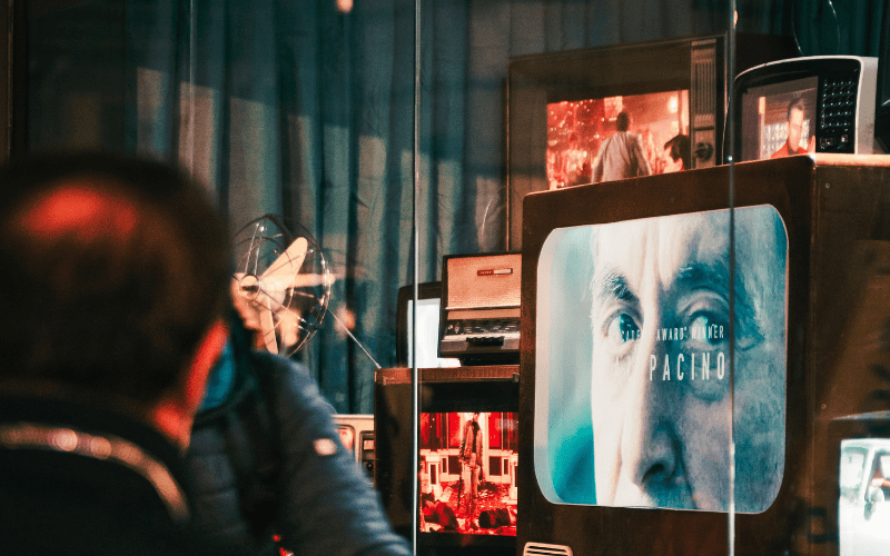 man looking at TV's in shop window