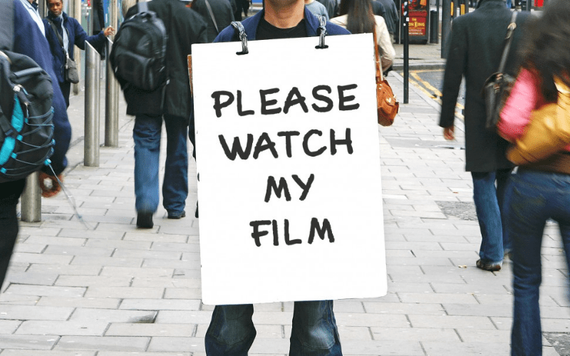 man holding a sign saying please watch my film